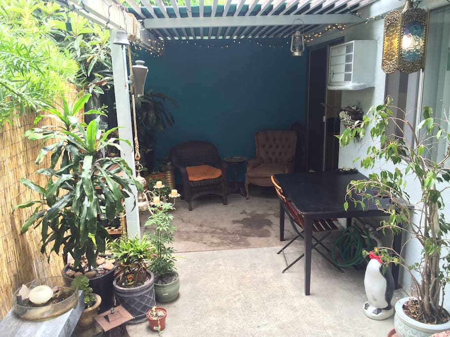 Plant filled patio with 2 comfy chairs under an awning. Perfect for reading or coffee.