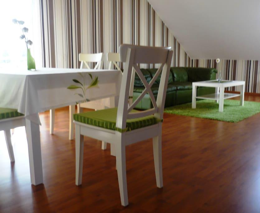 Gemütliches Wohnzimmer mit großem Esstisch und Flachbild-TV sowie zusätzlicher Schlafgelegenheit