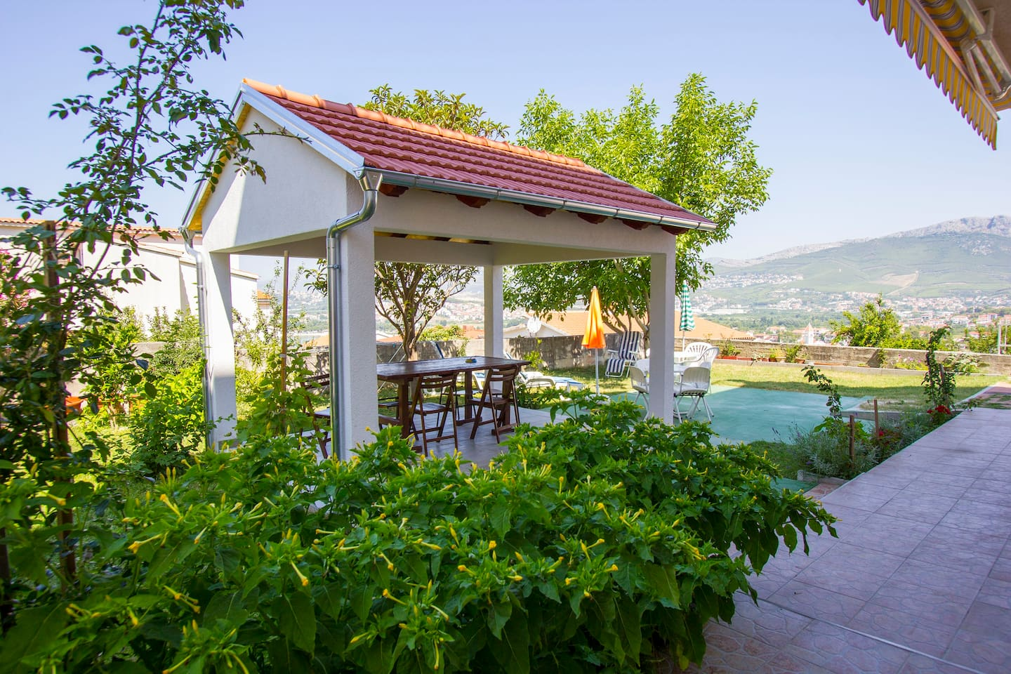 our big garden with table, chairs and barbecue where you can enjoy your meals and rest