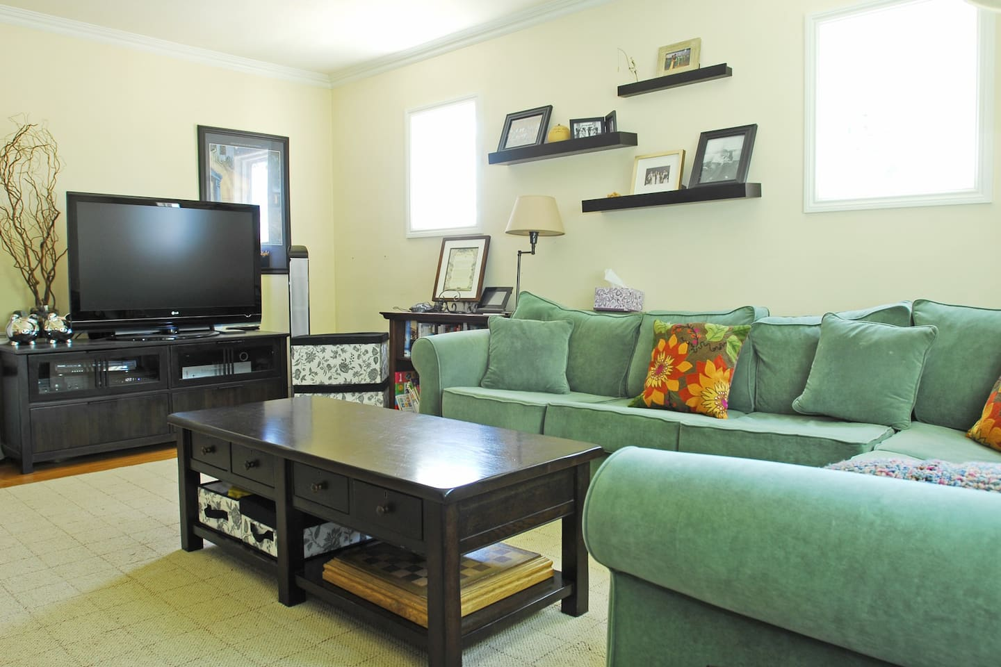 The front room includes a large TV with cable.  With Andrew moving in, the couch and TV are the same, but a chair and coffee table have changed.