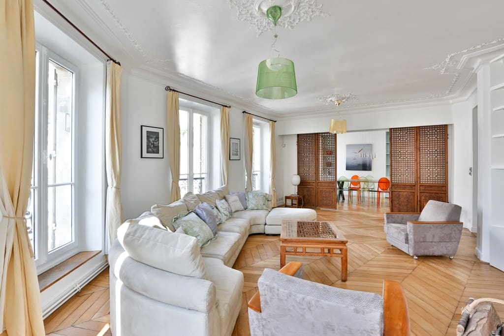 The 30 square meters living room has 5 double glazed windows facing street and leading to the balcony . It is equipped with : sofa, cable, TV, DVD, stereo, VCR, armchair, built-in shelves, built-in wall closet, decorative fireplace, hard wood floor.