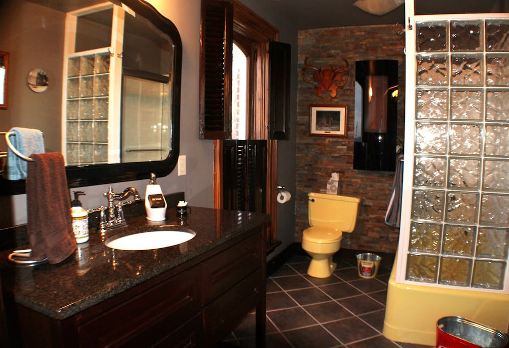 The attached bath is a modern moment in history. We saved the 1970 yellow tub and toilet and decorated to include the uniqueness while adding a manly feel with the electric fireplace and slate stone wall. Deer antlers and all.