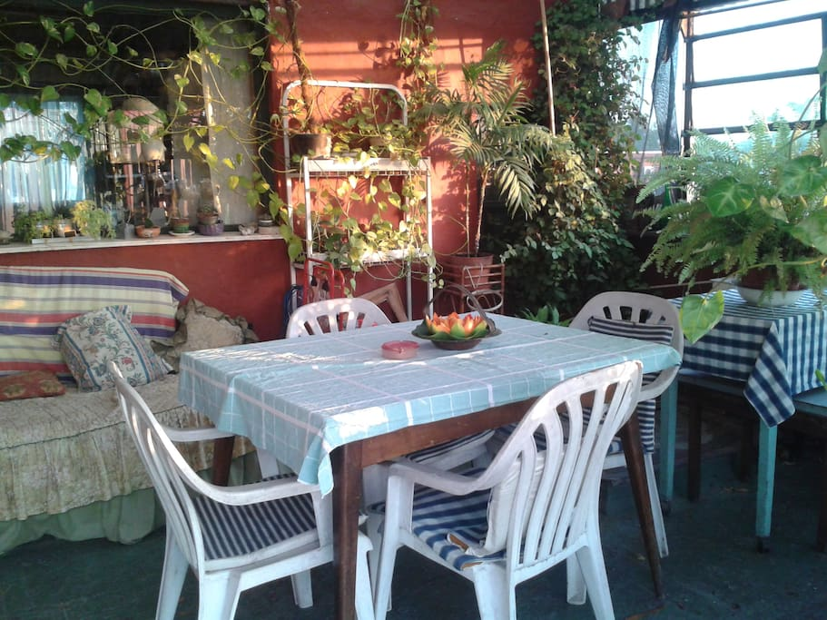 jardin de invierno techado con sillon cama, mesa y sillas