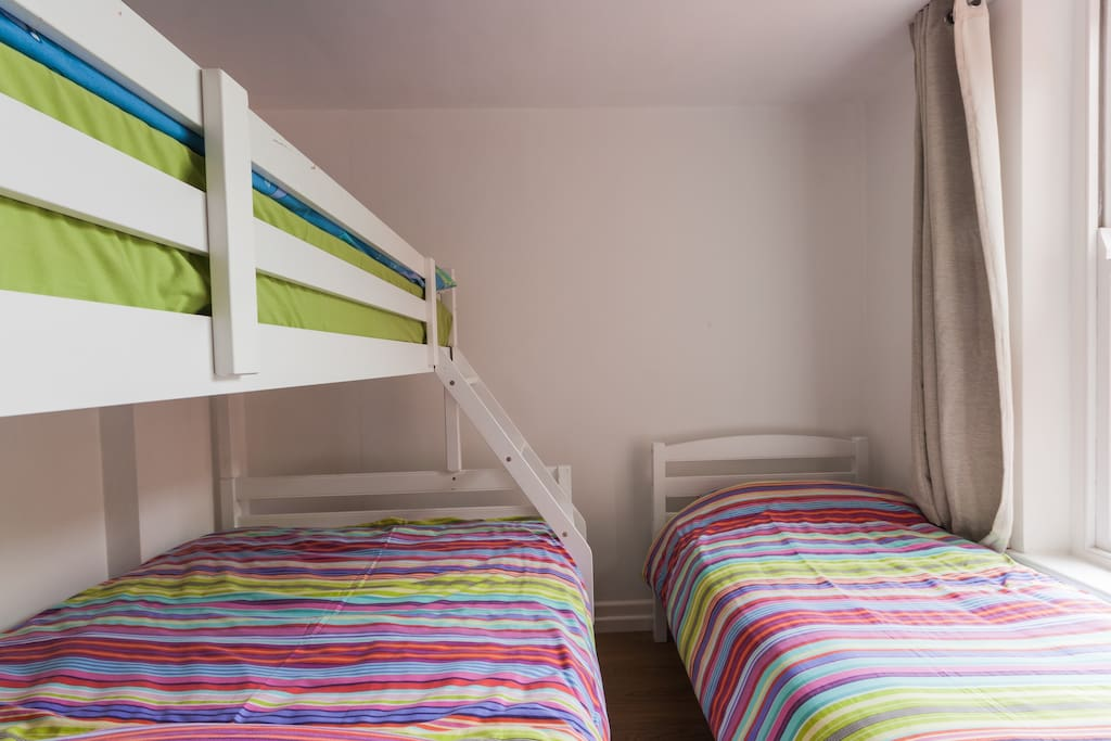 TRIPLE FAMILY ROOM, small double and two single beds beside HALL BATHROOM. This room has beds only and is suitable for kids or extra people. There are no tables, wardrobes etc.