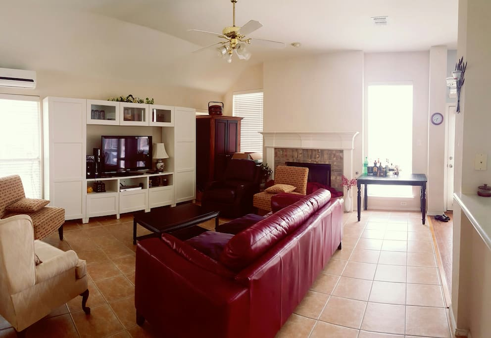 "Large living room with a 50"" tv and tons of chairs and a red leather couch that you can relax on!"