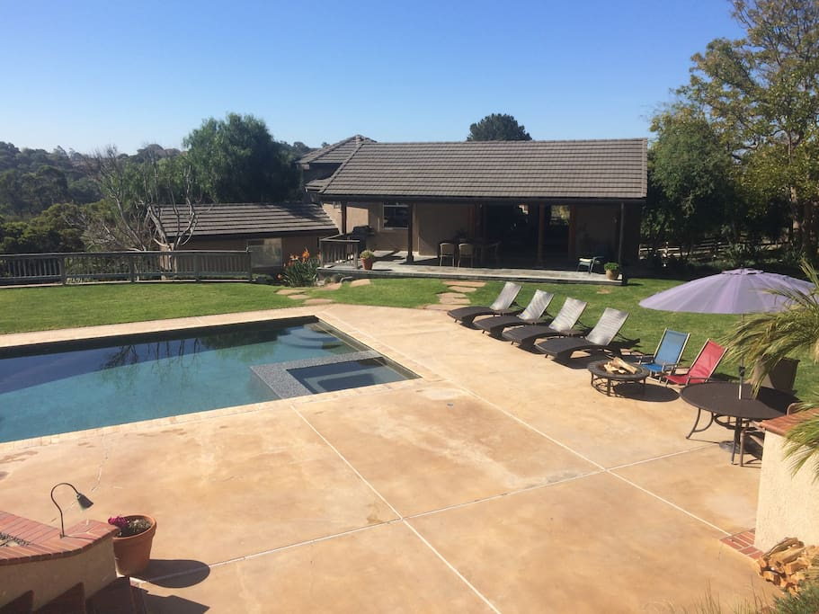 Front entry, large yard and garden area, pool, hot tub, and fire pit.