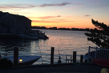 This waterfront (1/4 mile from the beach)  home sleeps 14, located on a private cul de sac, heated in ground pool, & 60 ft bulkhead. Four bedrooms, 3.5 bathrooms, outdoor shower, central AC, washer & dryer are some of the amenities. Amazing sunsets!