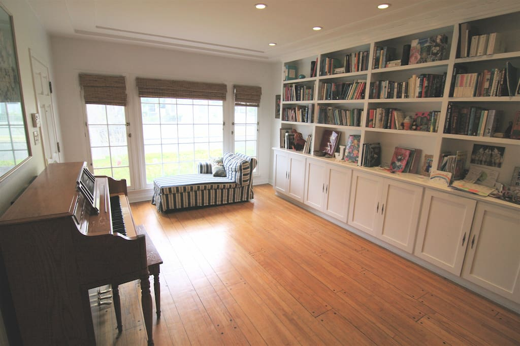 Original hardwood floors and library in front room upon entry.