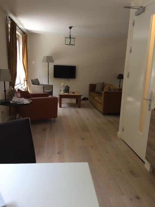 Grote woonkamer met tv en mooi uitzicht