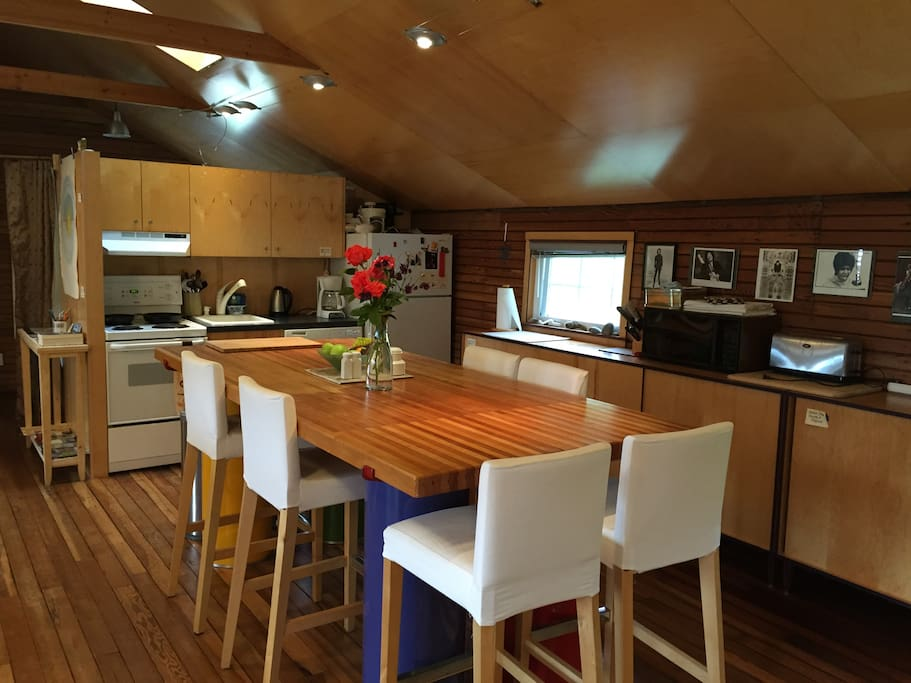 Cook together in well-stocked kitchen with huge custom-made table, upcycled from bowling alley