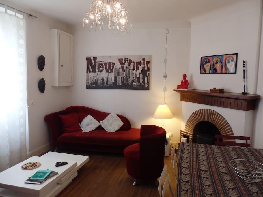 Autre point de vue du salon, de sa cheminée et du canapé lit. La table avec ses rallonges peut accueillir jusqu'à 10 pers.