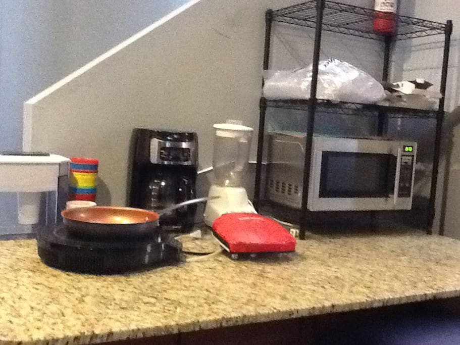 The kitchenette features small appliances for guest use: a hot plate, a coffee maker, waffle iron, blender, and microwave oven.