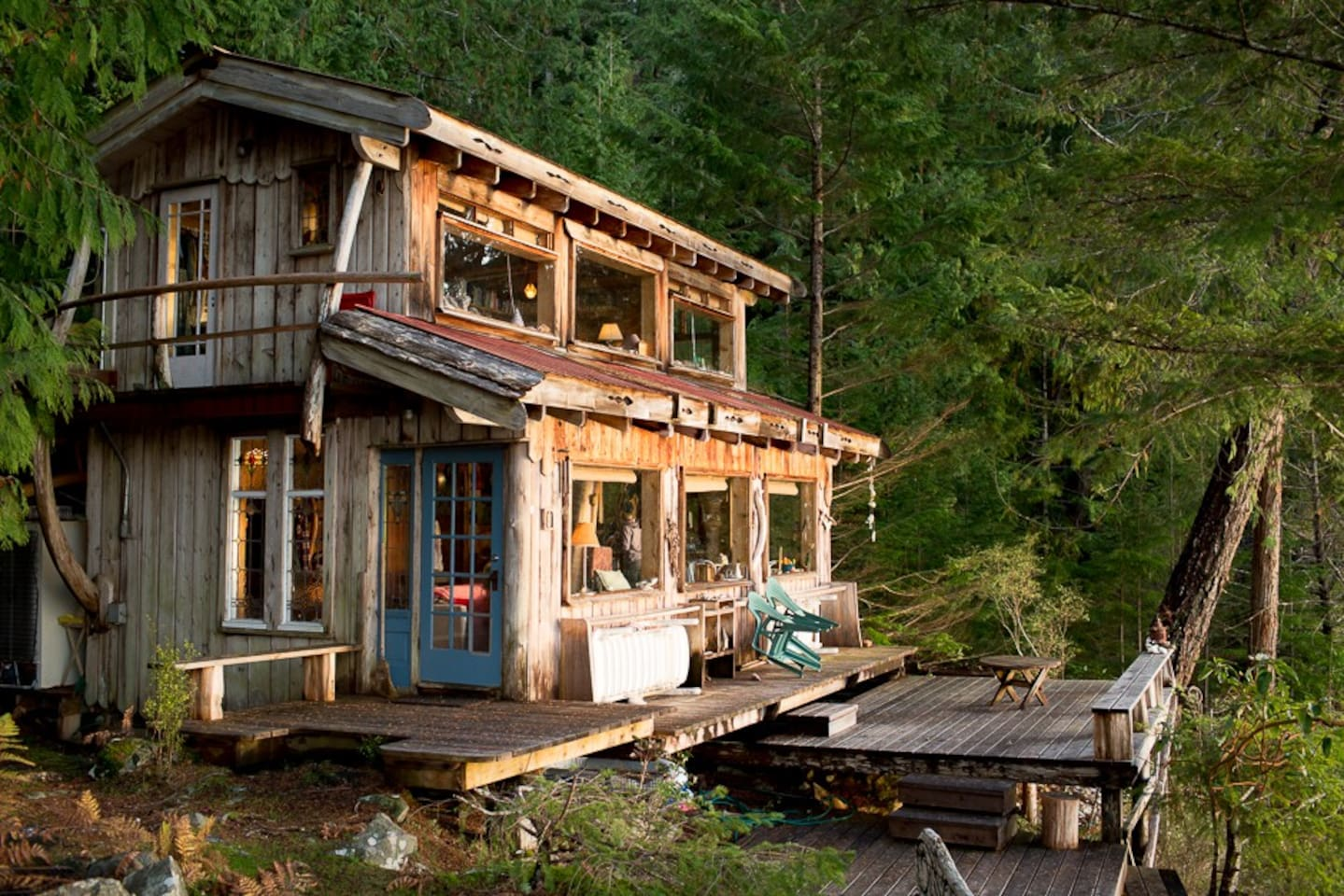 Cabin exterior, nestled in the trees with decks and windows overlooking Gorge Harbour.
