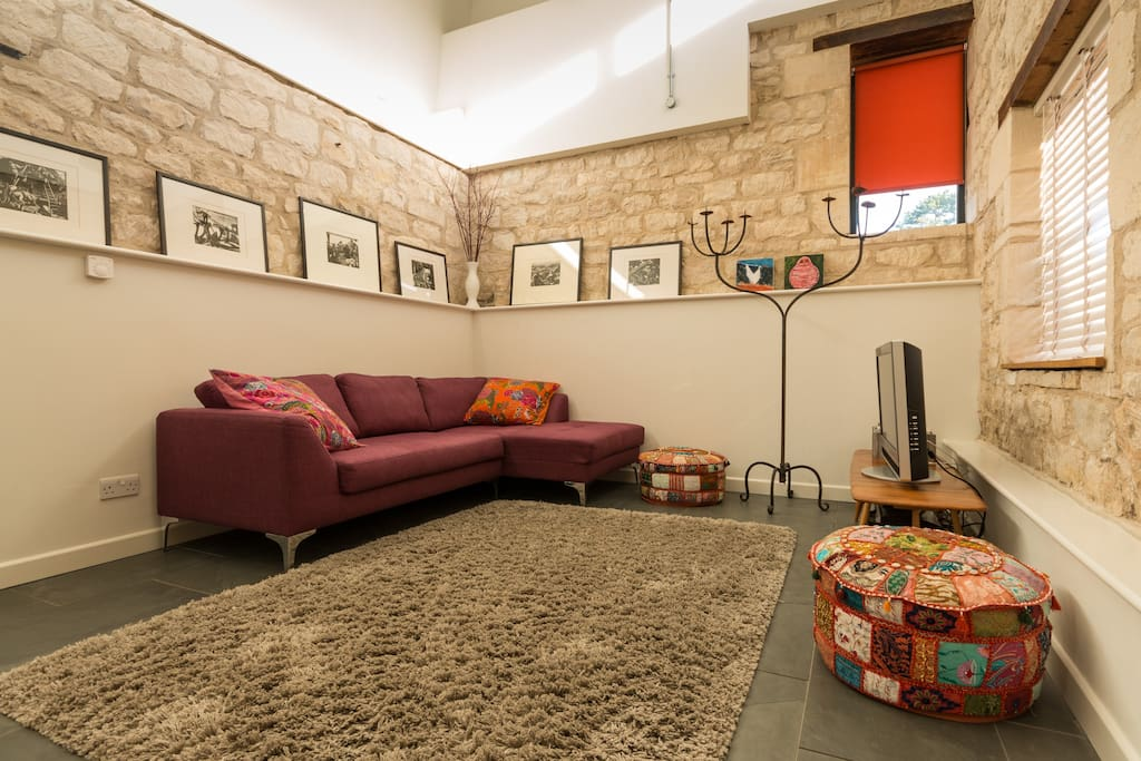 Double height sitting area with underfloor heating and exposed Cotswold stone walls