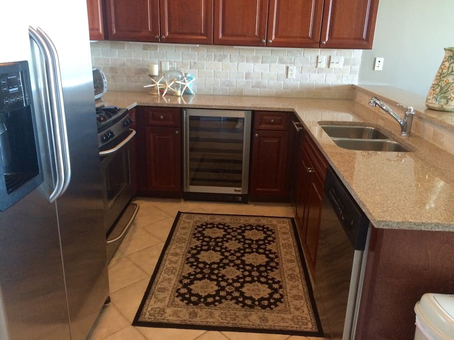 Fully stocked kitchen with dishes and pots. dishwasher, ice maker, wine fridge, gas stove and oven, microwave and full refrigerator!