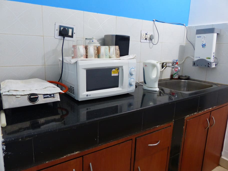 The kitchen with a gas stove, microwave, water purifier