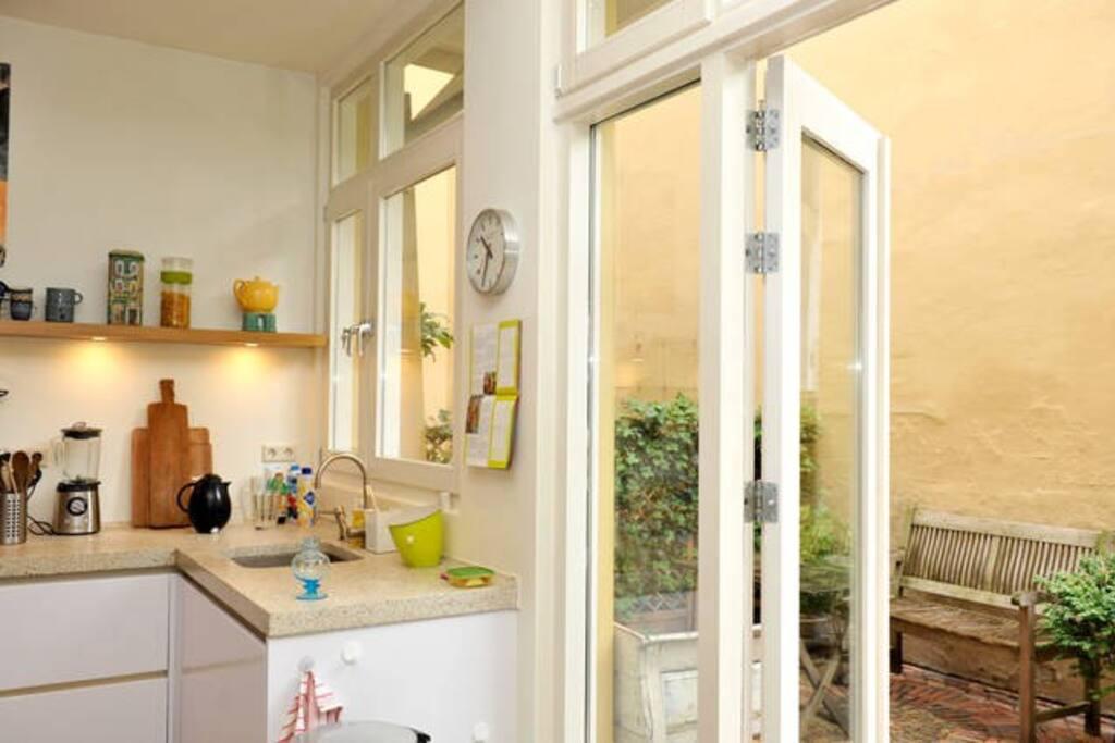 Modern kitchen with open doors to garden