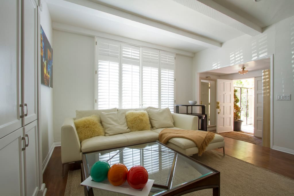 Spacious living room with cozy high-end furnishings. Entry foyer leads to private patio