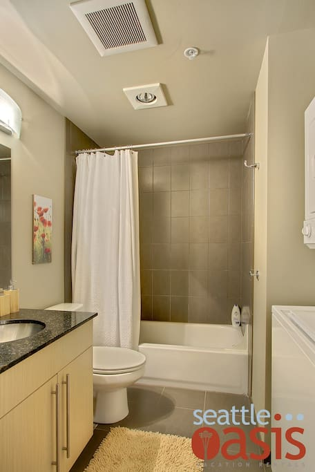 The crisp and clean bathroom also holds a washer/dryer unit.
