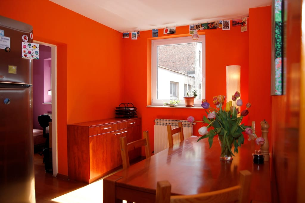 Dining room has lots of sunshine and its walls are orange that stimulates good feelings during the meals