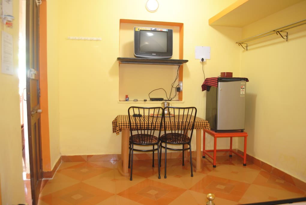Photo shows TV, fridge and table