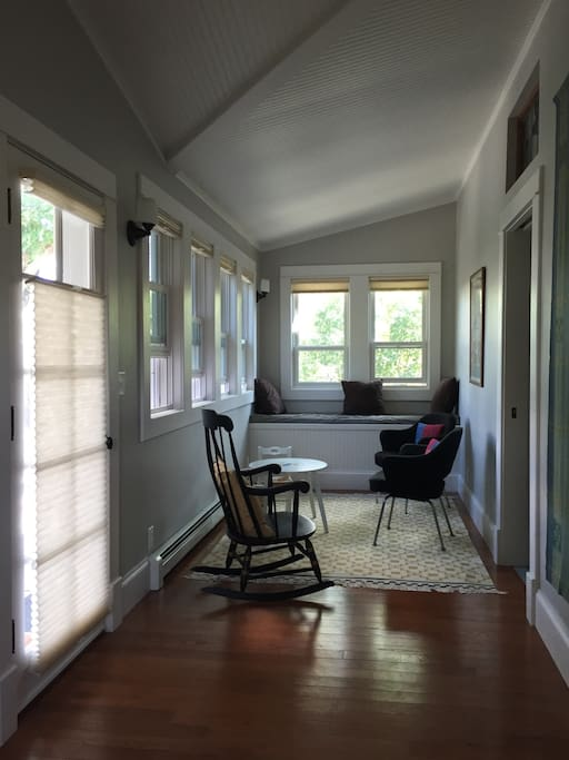 sunroom: saarinen chairs, window seat, view of porch and patio