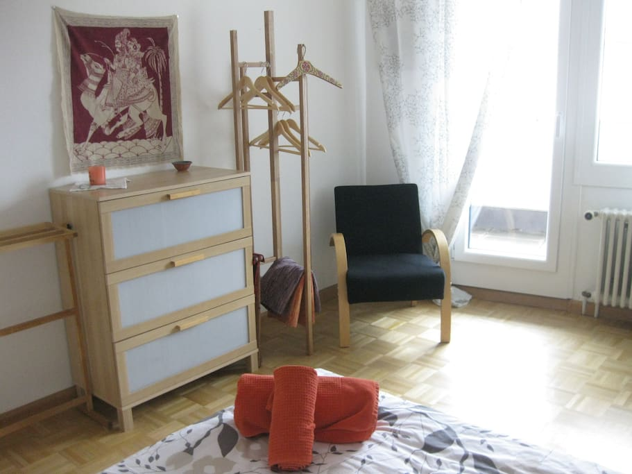 View of guest bedroom with chest, hangers and easy chair.