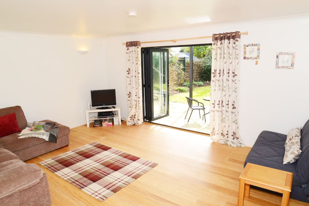 Lounge with double sofa bed, direct &access to the garden