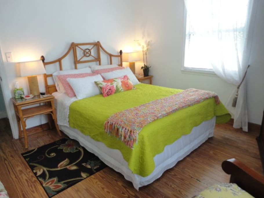 Queen bed at rear of house, armoir with TV, armchair, small dressing table