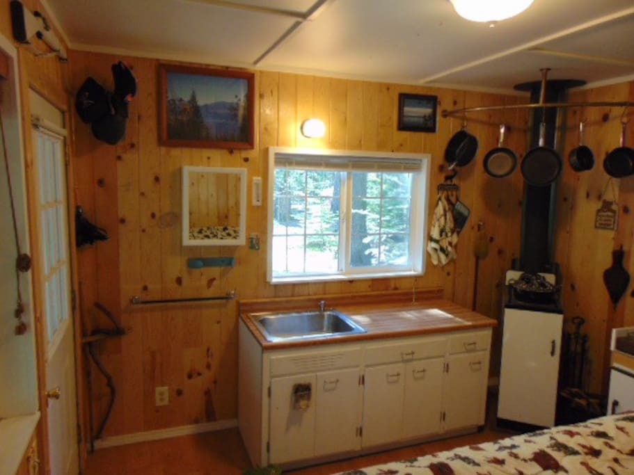 West facing wall: Medicine cabinet, sink, light, food prep area, stove, hanging pots.