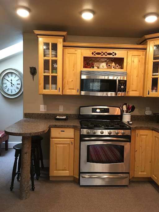 All full sized GE Profile appliances, breakfast bar with 2 bar stools. The bedroom door is to the right of the clock.