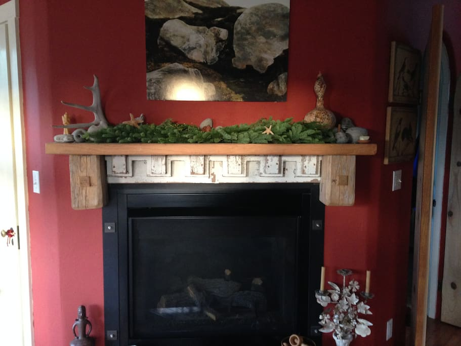 living room side of double sided fireplace adorned with greenery