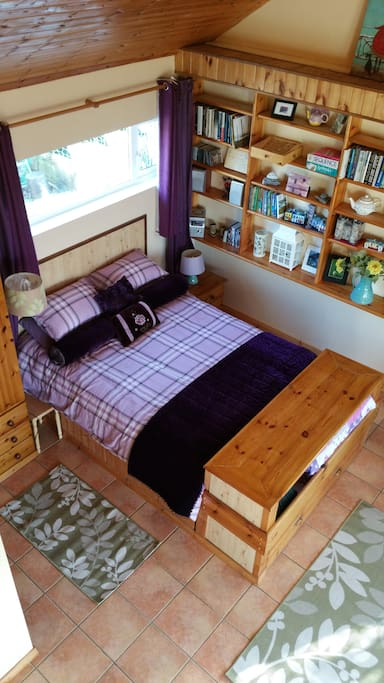 The king size bed with different linen taken from the loft area