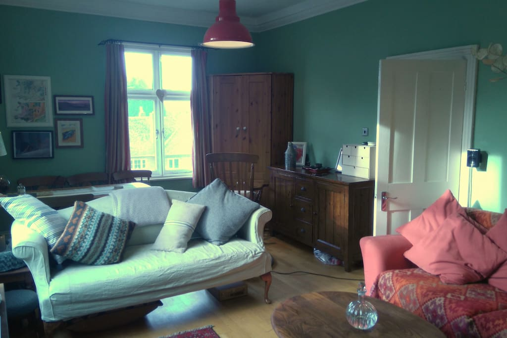 Light and airy Dual aspect sitting room with wooden floor and rugs throughout