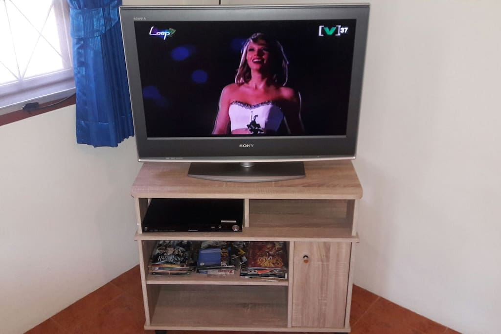 The large flat screen TV connected to cable and DVD/CD player.