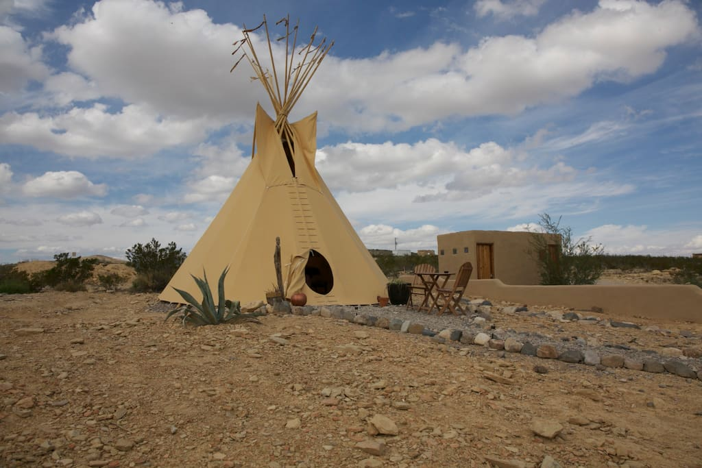 Outside view of tipi and bathroom. Sitting area outside with table and chairs.