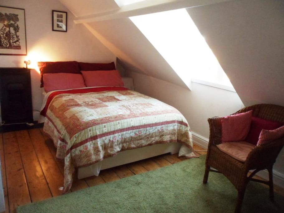 Bedroom and chair and attic window with cast iron fireplace.