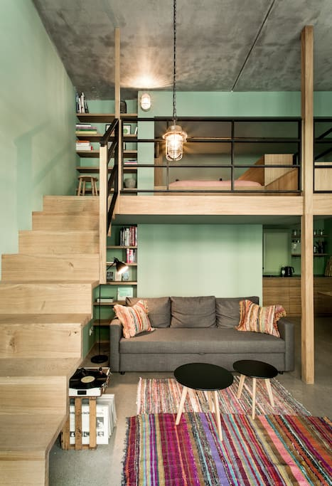 Solid oak staircase leading to the loft level with queen size bed (1.60m). Convertible sofa bed (1.40m) below. Find some of our favourite books on design, architecture and travel in the wooden book shelves, available for you during your stay.