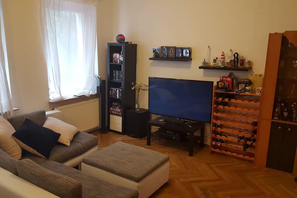 Wohnzimmer mit großer Couch und 60 Zoll TV