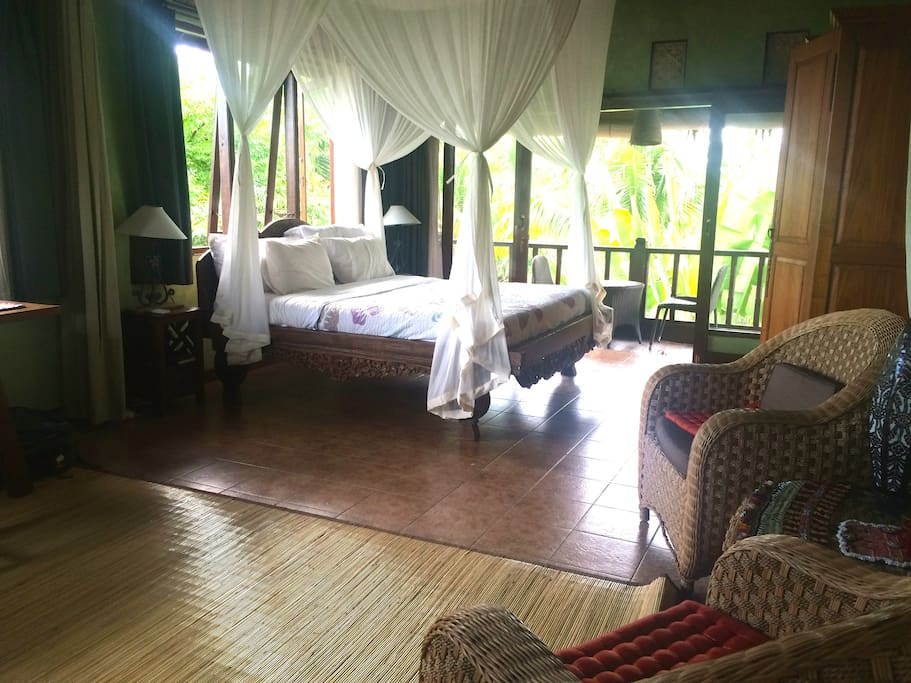 Large master bedroom on top floor of house has A.C. Upstairs bedroom features a hand carved king bed, rice paddy and jungle views , balcony, high ceilings. Half the room can be curtained off and used as desk and reading area. Very private.