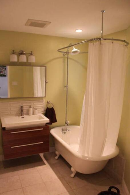 Spa like bathroom with Pottery Barn appliances, luxuriously restored claw foot tub, and Heath Ceramics designer tile